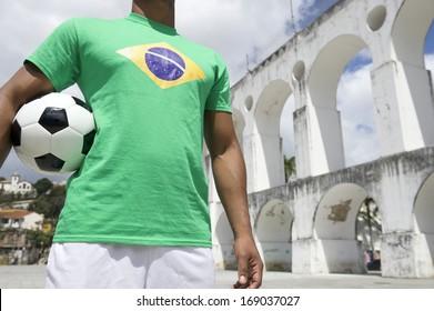 Brazilian football player holding soccer ball wearing Brazilian flag shirt at Lapa Arches in Rio de Janeiro
