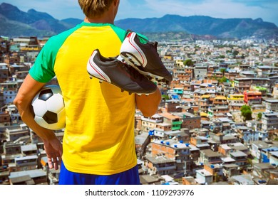 Brazilian football player standing in Brazil colors kit holding soccer ball in front of favela slum background in Rio de Janeiro