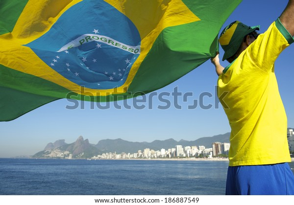 Brazilian football soccer player flying flag in front of Ipanema Beach city skyline Rio de Janeiro Brazil