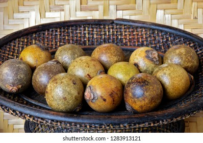 Brazilian fruit: stack of macauba on darkened wicker basket. Fruit palm is consumed in natura and produces excellent edible and industrial oils, including biodiesel