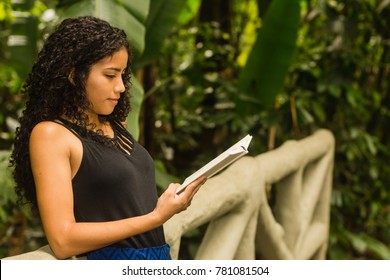 Brazilian girl with with curly hair reading a book serious pensive on a footbridge in a tropical forest. Happiness in nature and woman power concept. Space for text