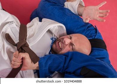 Brazilian jiu jitsu training in traditional kimono. Parterre and ground lock techniques