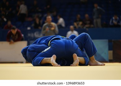 Brazilian Jiu-Jitsu BJJ judo tournament fight two fighters in blue gi kimono on the tatami in side control position