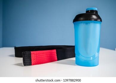 Brazilian JiuJItsu Black Belt BJJ and supplement shaker on the table at home