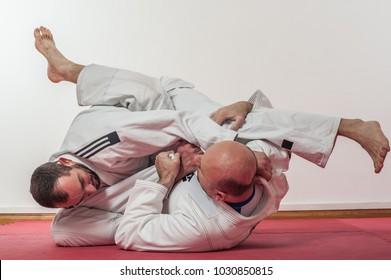 Brazilian jiu-jitsu training demonstration in traditional kimono. BJJ Sweep from guard