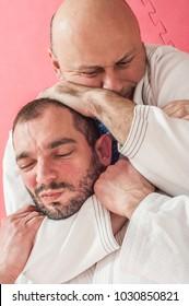 Brazilian jiu-jitsu training demonstration in traditional kimono. BJJ rear naked choke, RNC, Mata Leao