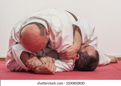 Brazilian jiu-jitsu training demonstration in traditional kimono. BJJ Americana lock from Mount position, Top Ude Garami