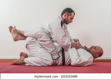 Brazilian jiu-jitsu training demonstration in traditional kimono.BJJ Closed guard position