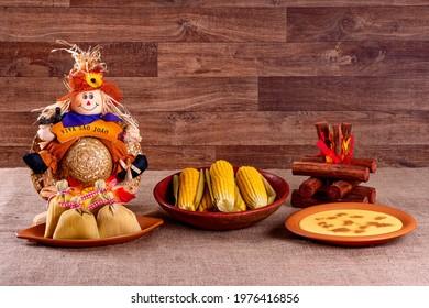"Brazilian june party. Typical foods of the June festival. hominy, boiled corn, corn cake, popcorn, broccoli, paçoca, genipapo and peanuts. It is written: ""Viva São João"" in Portuguese."