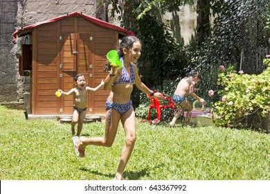 Brazilian kids playing with water in the backyard. Funny sun day.