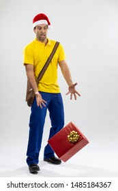 Brazilian mailman dressed as Santa Claus dropping a gift on a white background. copy space.