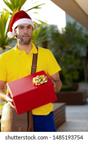 Brazilian mailman dressed as Santa Claus delivering a gift. Online purchase being delivered.