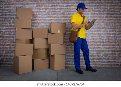Brazilian mailman with a tablet checking a lot of packages in a deposit