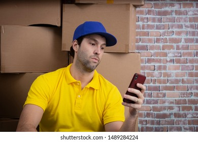 Brazilian mailman using a smartphone in a deposit with a a lot of boxes.