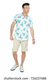 Brazilian male wearing a Hawaiian style floral shirt and beige shorts. Summer, tropical.