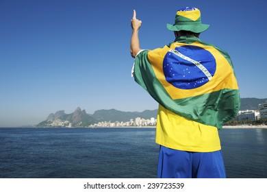 Brazilian man in Brazil colors wearing flag and hat in front of Ipanema Beach city skyline Rio de Janeiro Brazil