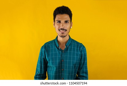 Brazilian man in a green social shirt, isolated on yellow backgr