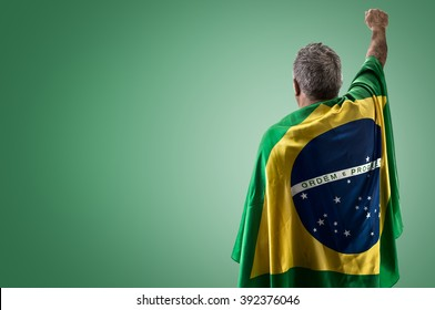 Brazilian man holding the flag of Brazil on green background