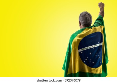 Brazilian man holding the flag of Brazil on yellow background