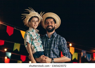Brazilian man and son wearing traditional clothes for Festa Junina - June festival
