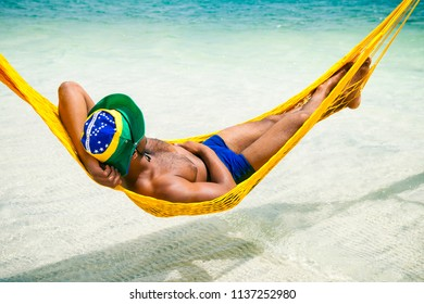 Brazilian man in sunga bathing suit and brazil flag hat relaxing in seaside beach hammock in Brazil. Translation: Order and Progress