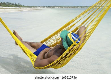 Brazilian man in sunga bathing suit relaxing in seaside beach hammock in Brazil