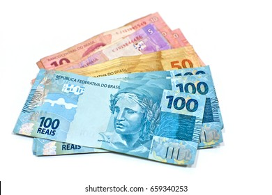 Brazilian money bills (One hundred, Fifty, Ten and Five Reais) isolated on white background. Money and finance concept.