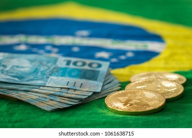 Brazilian money and bitcoins against the Brazilian flag