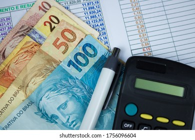 Brazilian money with calculator and numerical chart background.