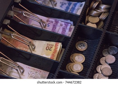 Brazilian money notes and coins inside the electronic cash register