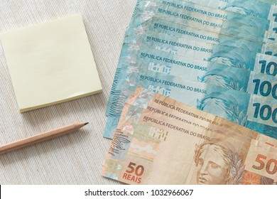 Brazilian money with a pencil and a piece of paper with space for an inscription
