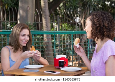 Brazilian multiethnic girl friends eating pao de queijo and coxinha food snack outdoors in the city of Sao Paulo during summer day bright light.
