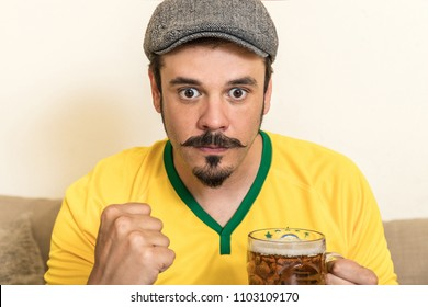 Brazilian mustache fan watching on had sat on the sofa playing the glass drinking a cold beer. Team brazil supporter watching the soccer world cup with the yellow jersey tense and apprehensive