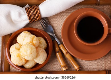 Brazilian snack pao de queijo (cheese bread) on brown plate with  cup of coffee on bamboo tray. Selective focus
