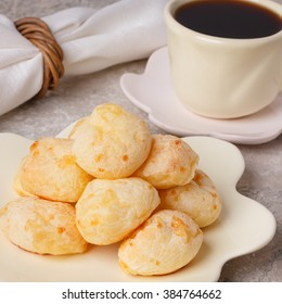 Brazilian snack pao de queijo (cheese bread) on white plate with  cup of coffee on marble table. Selective focus