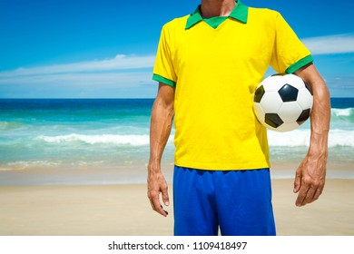 Brazilian soccer player in Brazil colors holding football tropical Ipanema Beach Rio de Janeiro