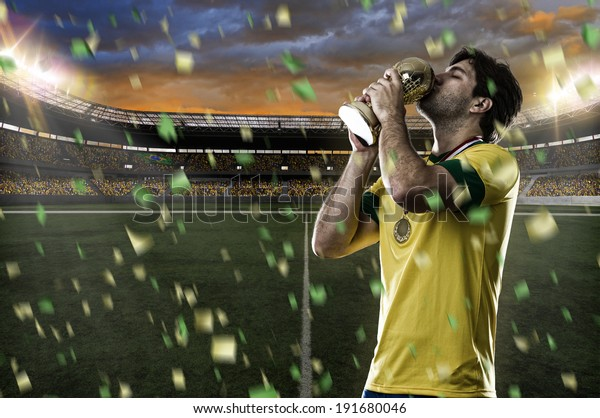 Brazilian soccer player, celebrating the championship with a trophy in his hand.
