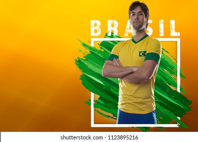 Brazilian soccer player, celebrating on a yellow background with copy space.