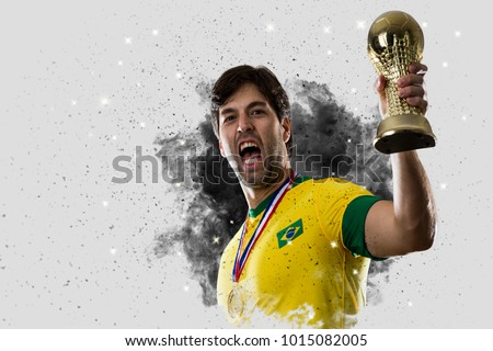 Brazilian soccer player coming out of a blast of smoke. celebrating with a trophy in his hand.