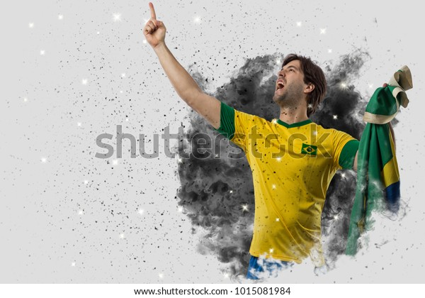 Brazilian soccer player coming out of a blast of smoke. celebrating.