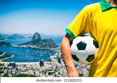 Brazilian soccer player holding football wearing shirt in Brazil colors at Rio de Janeiro skyline with Sugarloaf Mountain