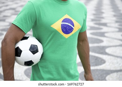 Brazilian soccer player holding football wearing Brazil flag t-shirt at Copacabana Beach boardwalk Rio de Janeiro
