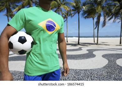 Brazilian soccer player holding football wearing Brazil flag t-shirt at Copacabana Beach boardwalk, Rio de Janeiro.