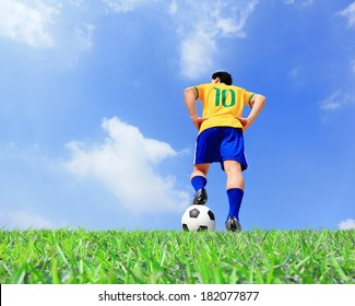 Brazilian soccer player man striking the ball at the stadium with blue sky
