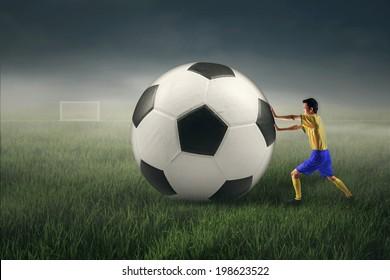 Brazilian soccer player pushing a big soccer ball