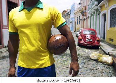 Brazilian soccer player standing on colonial Bahia street Pelourinho Salvador with vintage football