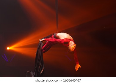 Brazilian strong sexy man do performance on aerial silks in red lights.  Sport training gym and lifestyle concept. Black background. Gymnast upside down on aerial silk