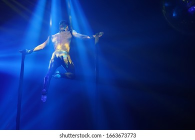 Brazilian strong sexy man do performance on aerial silks in blue lights.  Sport training gym and lifestyle concept. Black background