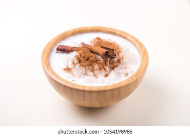Brazilian sweet winter festival dessert Canjica. White corn porridge with cinnamon and coconut. Selective focus. Horizontal view.