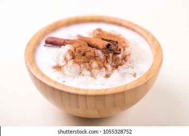 Brazilian sweet winter festival dessert Canjica. White corn porridge with cinnamon and coconut. Selective focus. Horizontal view.